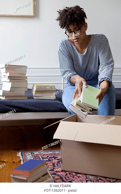 Young woman packing books in cardboard box at home