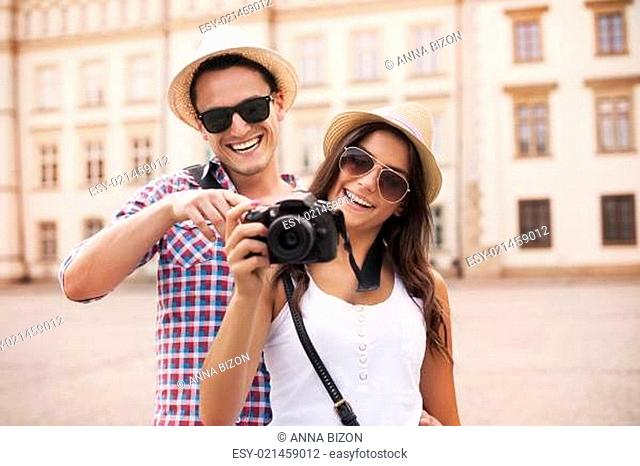 Smiling couple viewing pictures on the camera