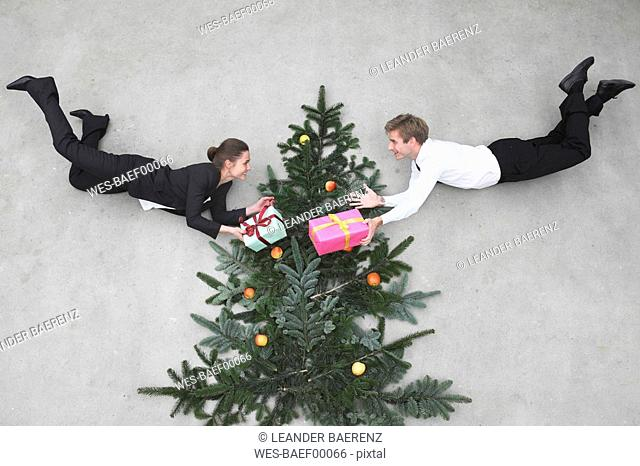 Businessman and businesswoman flying in front of christmas tree, holding presents, smiling, portrait, elevated view