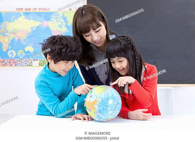 Young teacher and students looking at the globe and studying