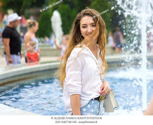 A young girl with a great mood walks by the fountain
