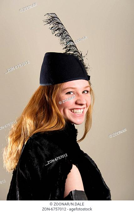 Laughing redhead in feathered hat and coat