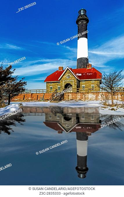 Fire Island Lighthouse - Fire Island Lighthouse and reflection in a pool of water from the melted snow after a snowfall