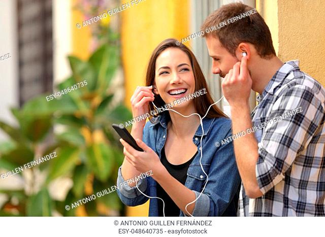 Happy couple sharing music from smart phone in a colorful street