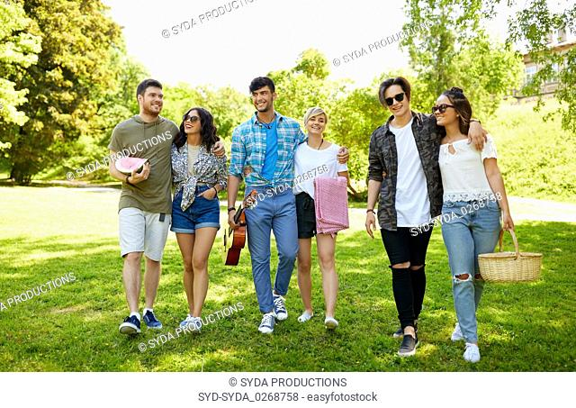 friends with guitar going to picnic at park