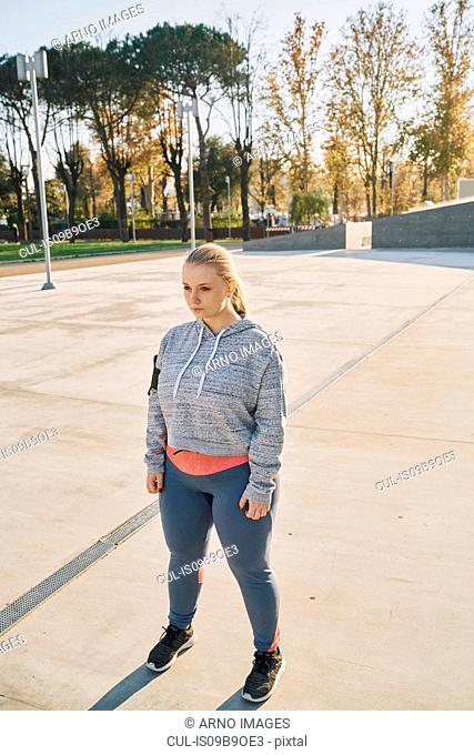 Curvaceous young woman training, standing staring