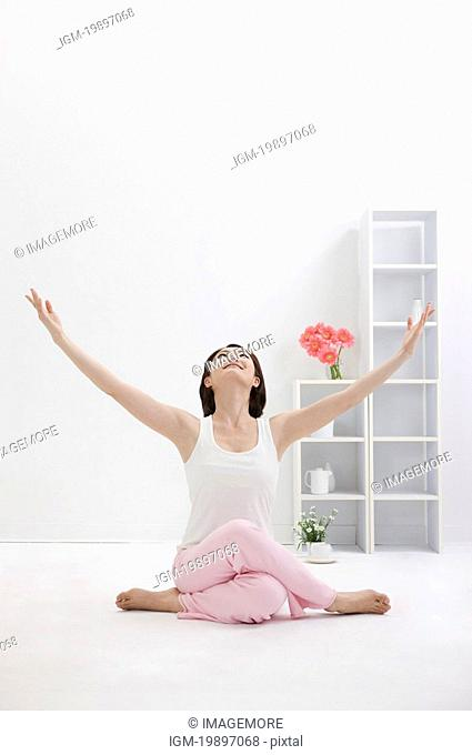 Young woman doing yoga with arms outstretched