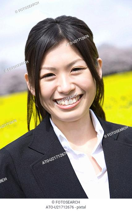Smiling Businesswoman In Rape Blossoms, Portrait, Front View, Differential Focus