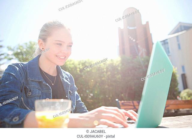Teenage girl sitting outdoors using laptop computer, looking down smiling, Reykjavik, Iceland