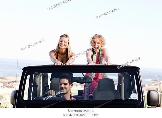 Women standing in jeep on road trip