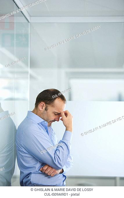 Businessman contemplating against reflective wall