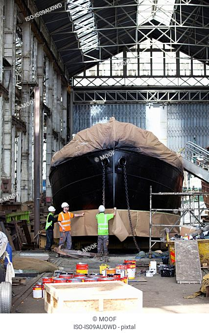 Three workers wrapping boat in shipyard
