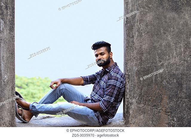 Male model sitting on a rock ledge looking at camera, Sion fort, Mumbai, Maharashtra