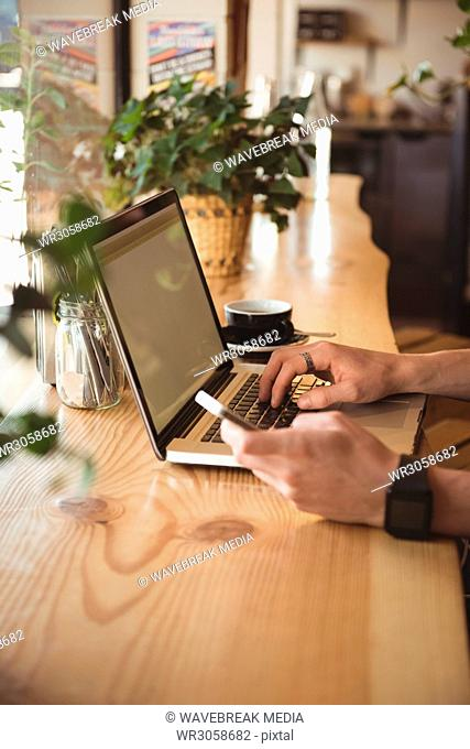 Mid section of man using mobile phone and laptop at table