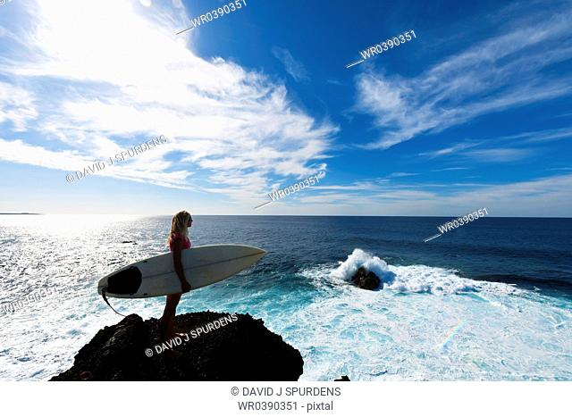 A sufer stands and looks out to sea