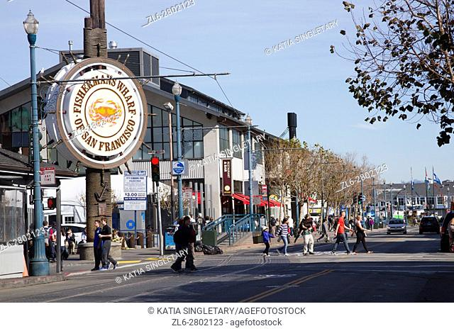 People stroll at Fishermans's Wharf in San Francisco, California. Famous Fisherman Wharf circular sign in the famous tourist section of San Francisco