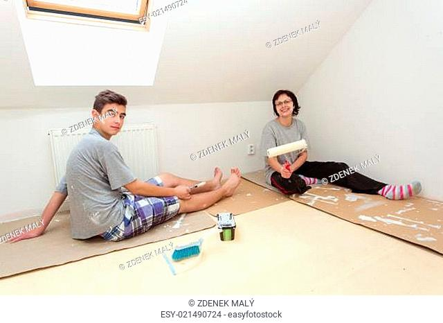 housewife with son resting after painting wall to white at home
