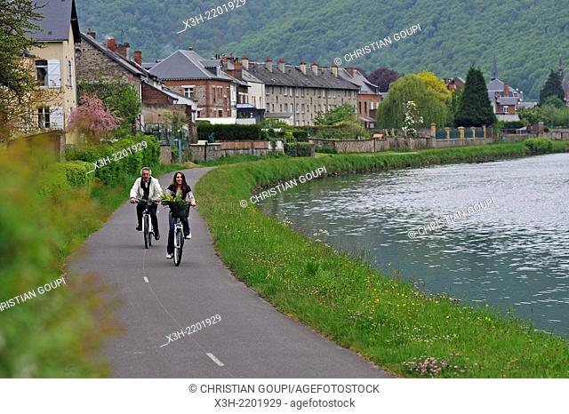 young woman and a man cycling on cycle lane along the Meuse River at Haybes, Ardennes department, Champagne-Ardenne region of northeasthern France, Europe