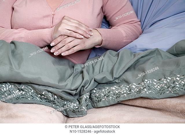 Young woman's hands as she sits in her bed