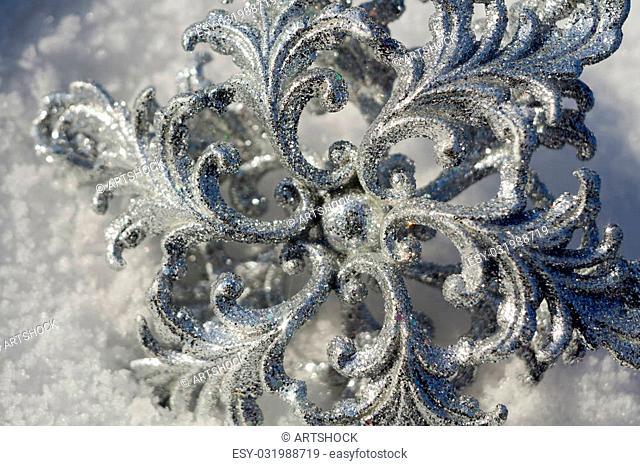Ornamental silver snowflake glittering on fresh white snow
