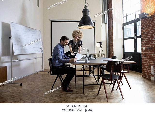 Man and woman discussing document in boardroom