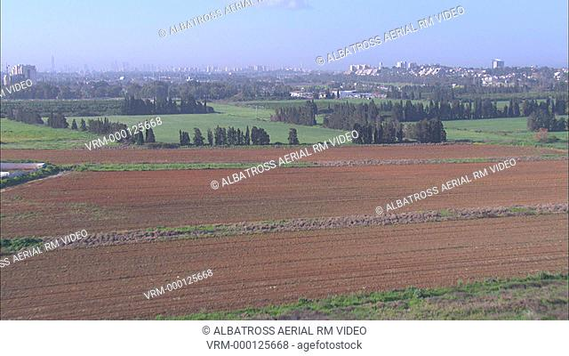 Aerial of fields and orchards; rural landscape. City or urban area in background