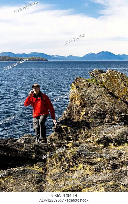 Man talks on his smart phone along the rocky shores of Tongass Narrows, Ketchikan, Southeast Alaska, Spring