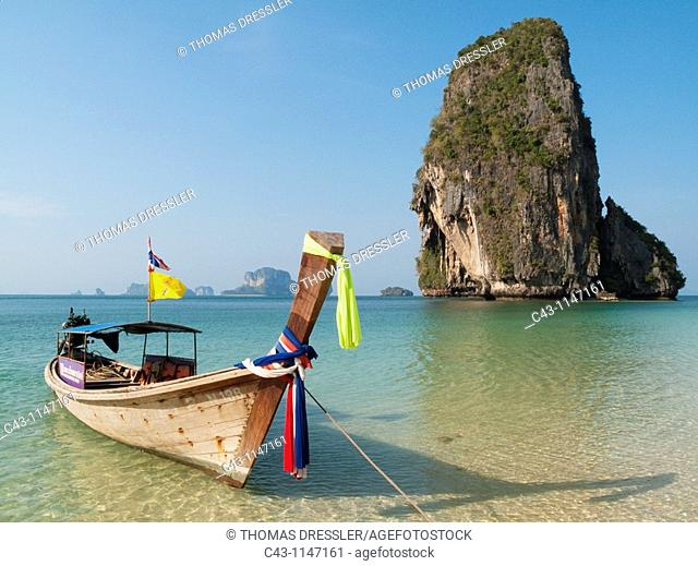 Thailand - Long-tail boat at the sandy Phranang Beach and limestone cliffs in the Andaman Sea  Phranang Peninsula, Krabi province, Southern Thailand