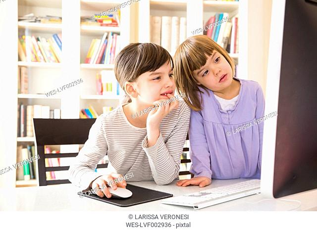 Two sisters spending time together at computer