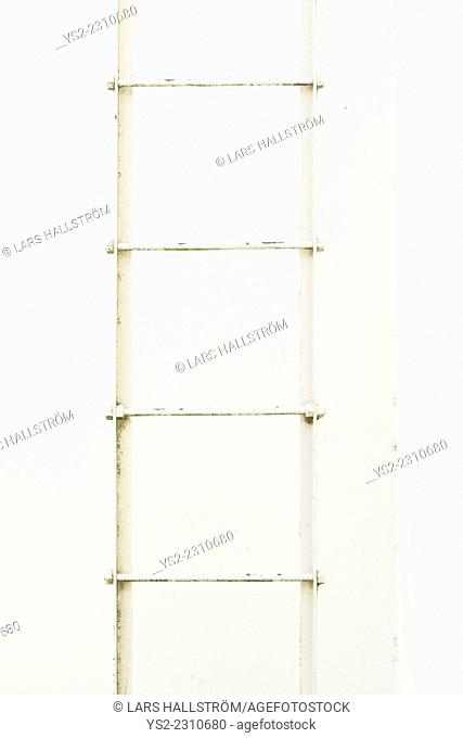 Empty iron ladder and white stone wall