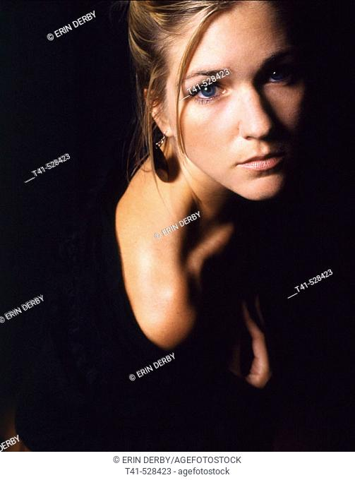 A blue-eyed woman in black couture. Shot on 120 film