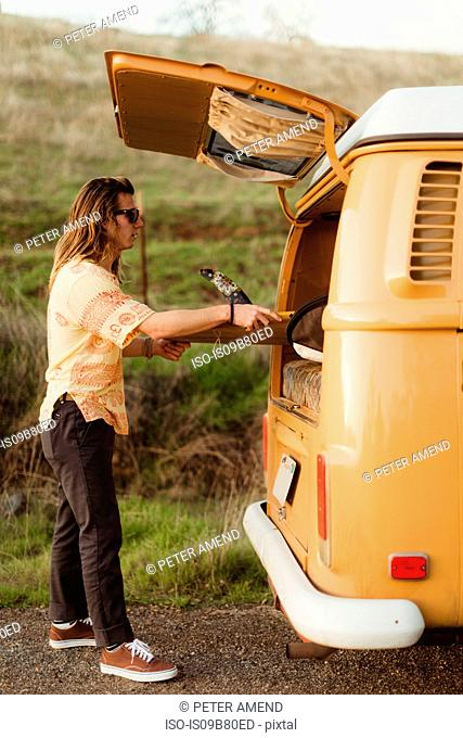 Young male surfer removing surfboard from vintage recreational vehicle, Exeter, California, USA