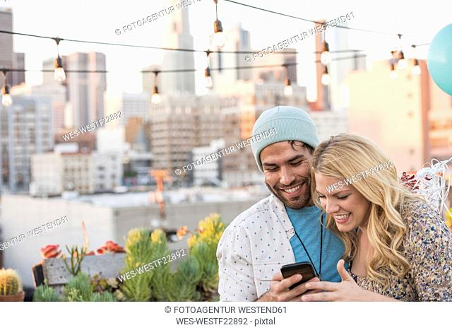 Young couple with balloons standing on rooftop terrace, using smart phone