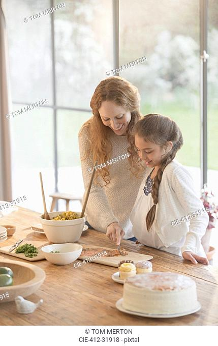 Pregnant mother and daughter preparing food at dining table