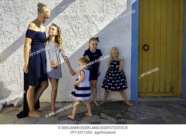 candid family portrait, mother with four daughters in front of house wall. Australian ethnicity