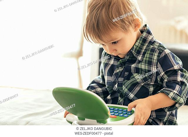 Boy using toy laptop
