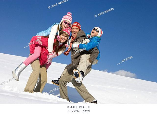 Parents giving children piggyback ride while standing in snow