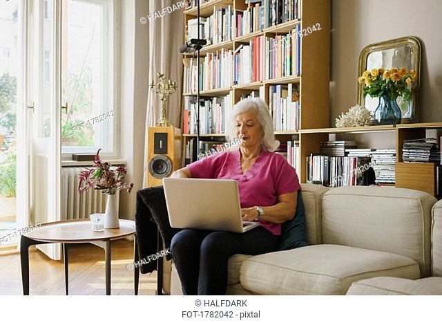 Senior woman using laptop on living room sofa