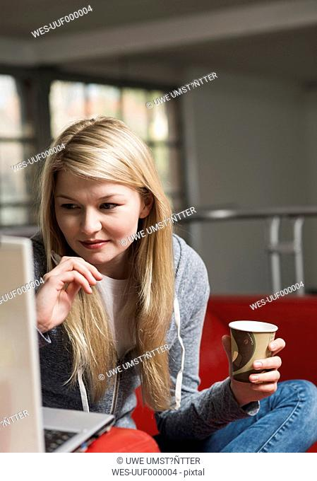 Portrait of young woman using laptop