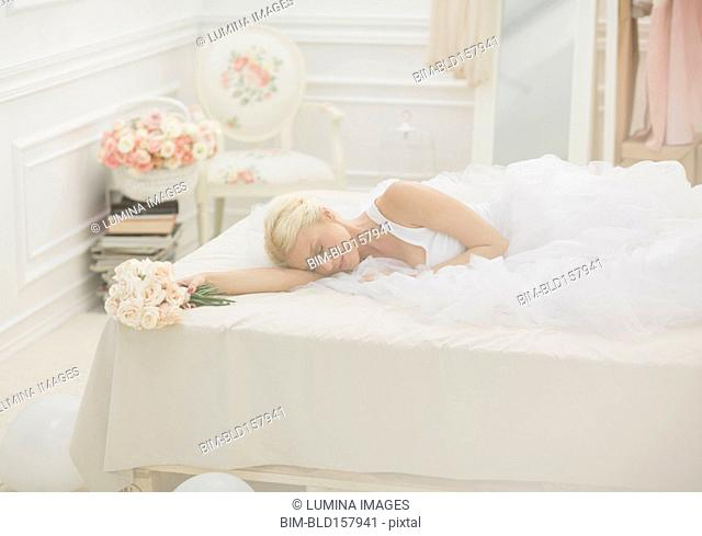 Bride sleeping on bed with bouquet of flowers
