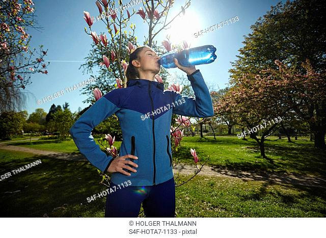 Sportliche Frau trinkt Wasser in einem Park im Frühling