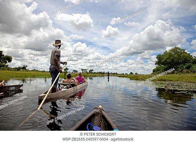 Touristen auf einem traditionellem Mokoro Boot im Okavango Delta, Botswana, Afrika   tourists on a traditional mokoro boat in the Okavango Delta, Botswana
