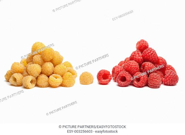 Yellow and red raspberries on white bacground