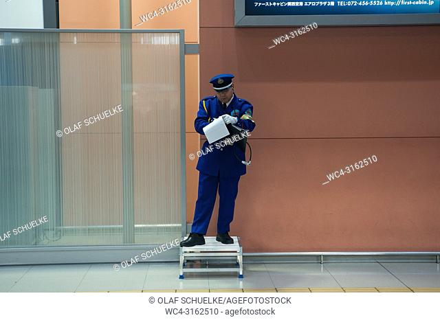 23. 12. 2017, Osaka, Japan, Asia - A uniformed airport staff is seen making notes while he stands on a small pedestal at Kansai International Airport