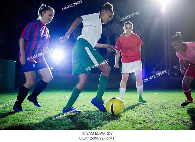 Young female soccer players playing soccer on field at night, kicking the ball