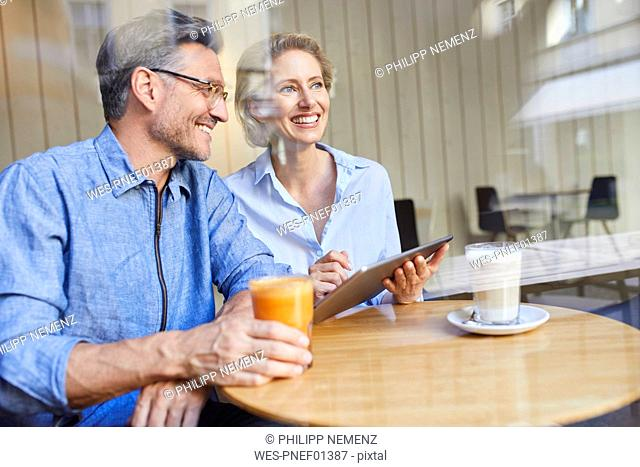 Happy woman and man using tablet in a cafe
