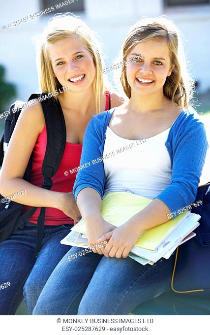 Two Female College Students Sitting On Bench With Textbook