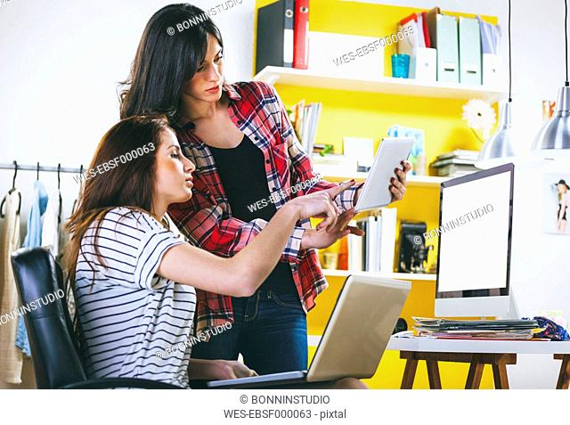 Two female fashion bloggers with computer, laptop and digital tablet in the office