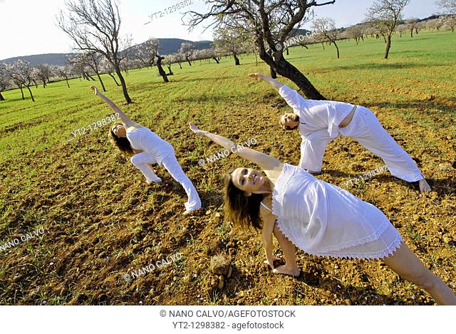 Three people, one sweedish man, a brazilian woman and a spanish woman, practicing yoga in the fields of Ibiza, Spain