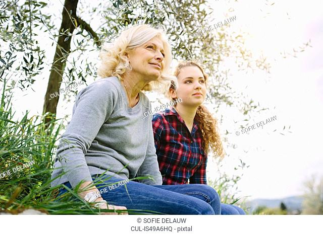Mother and teenage daughter sitting on grass